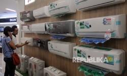 Pengunjung toko elektronik sedang memperhatikan pendingin ruangan.