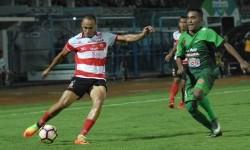 Pesepak bola Madura United (MU) Piter Osaze Odem Wingie (kiri) dibayangi pesepak bola PS TNI Mohammad Kasim Slamat (kanan) berusaha menendang bola dalam pertandingan kompetisi Liga 1 di Stadion Gelora Bangkalan, Bangkalan, Jawa Timur, Jumat (19/5).