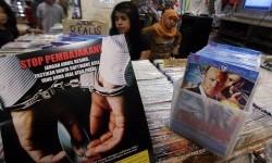 Petugas Ditjen HKI (Hak Kekayaan Intelektual) KemenKumHam menempelkan gambar sosialisasi Anti Pembajakan di toko - toko penjual Software dan DVD Bajakan di Mall WTC Serpong, Serpong, Tangerang Selatan, Banten, Rabu (19/6).