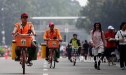 Petugas kebersihan mengendarai sepeda saat berpatroli di kawasan Hari Bebas Kendaraan Bermotor di Jakarta, Ahad (13/8).