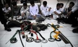 Petugas kepolisian memperlihatkan sejumlah barang bukti senjata tajam yang disita dari pelajar yang melakukan tawuran.