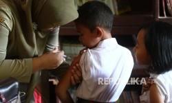 Petugas medis melakukan imunisasi kepada seorang anak.