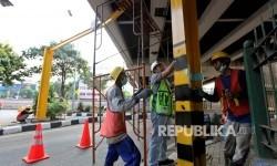 Petugas melakukan perbaikan pada tiang palang di Jalan Kapten tendean, Jakarta Selatan, Ahad (13/8).