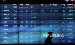 Petugas melintasi papan elektronik yang menunjukkan pergerakan indeks harga saham gabungan (IHSG) di gedung Bursa Efek Indonesia, Jakarta, Kamis (7/9).