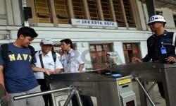Petugas membantu calon penumpang kereta api listrik (KRL) menggunakan tiket elektronik (e-ticketing) di Stasiun Jakarta Kota, Selasa (23/4).