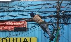 Petugas mengecek instalasi kabel di tiang listrik milik PLN di Benhil, Jakarta, Kamis (3/3).