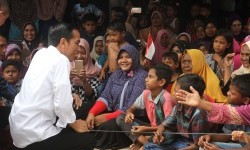 President Joko Widodo (left) greet children who were displaced at the Meurah Dua Village, Meureudu, Pidie Jaya, Aceh, on Friday (12/9).