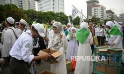 Relawan membagikan makanan dan minuman kepada peserta aksi super damai 212 di Jalan MH Thamrin, Jakarta, Jumat (2/12).