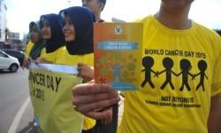 Salah satu peserta aksi menunjukkan selebaran sosialisasi tentang kanker pada aksi hari kanker sedunia.