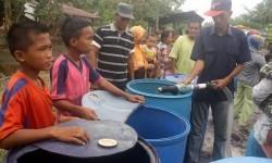 Sejumlah anak dan ibu-ibu dengan sabar antre pembagian air bersih, di Desa Rege Lestari Kecamatan Teluk Sampit Kabupaten Kotawaringin Timur, Kalteng, Minggu (4/10).