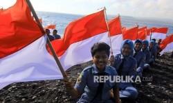 Sejumlah pelajar membawa bendera merah putih di Pantai Watu Dodol, Banyuwangi, jawa Timur, Sabtu (12/8).  Ratusan siswa pelayaran dan kelautan tersebut merayakan HUT ke-72 Indonesia dengan mengibarkan bendera merah putih di pantai.