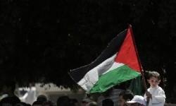 Seorang anak tengah memegang bendera Palestina di Gaza.