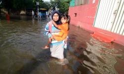 Seorang ibu menggendong anaknya yang akan berangkat ke sekolah menembus banjir di Perumahan Ciledug Indah 1, Tangerang, Banten, Rabu (22/2). Luapan Kali Angke menyebabkan ratusan rumah di kawasan perumahan tersebut terendam banjir hingga setinggi 60 cm.