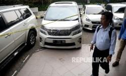 Seorang melintas disamping mobil sitaan milik bos First Travel yang merupakan tersangka untuk kasus penipuan dan penggelapan,pencucian uang serta pelanggaran Undang-undang Informasi dan trasnsaksi Elektronik (ITE), di halaman Bareskrim Polri, Jakarta, Senin (14/8).