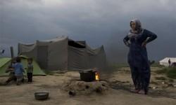 Seorang perempuan Suriah memasak di kamp pengungsi.