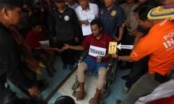 Seorang tersangka pembunuhan sekeluarga Andi Lala (tengah) memperagakan adegan memakai narkoba bersama rekannya Roni (kiri) sebelum membunuh korban saat menjalani reka ulang kasus di Mabar Medan, Sumatera Utara, Senin (8/5).