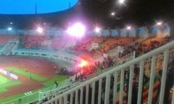 Suporter Indonesia di tribun selatan menyalakan suar di Stadion Pakansari setelah pertandingan Indonesia vs Myanmar, Selasa (21/3).