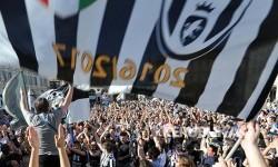 Supporter Tim Juventus merayakan kemenangan meraih gelar juara liga enam kali berturut-turut di Turin, Ahad (21/5).