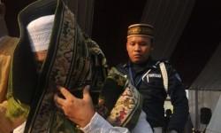 Tersangka penerima suap Hak Guna Usaha kelapa sawit Bupati Buol Amran Batalipu menutup mukanya dengan sejadah menuju mobil tahanan usai mengikuti shalat ied bersama tahanan lainnya di LP Cipinang, Jakarta Timur, Ahad (19/8)
