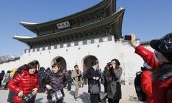 Turis berfoto dengan latar Istana Gyeongbok di Seoul, Korea.