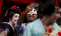 Turis mengenakan kimono melakukan selfie di Kuil Sensoji, Tokyo, Jepang.