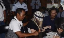 Warga Australia terpidana 20 tahun penjara dalam kasus penyelundupan mariyuana, Schapelle Leigh Corby (tengah) menutup wajahnya saat melengkapi administrasi bebas bersyarat di Kejaksaan Negeri Denpasar, Bali, Senin (10/2).   (Antara/Nyoman Budhiana)