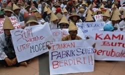 Warga Kabupaten Rembang pendukung pembangunan pabrik semen membentangkan poster saat berunjuk rasa di Semarang, Jawa Tengah, Selasa (13/12).