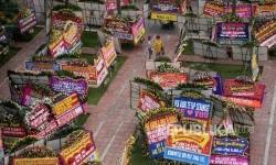 Warga melintas di antara karangan bunga yang ditujukan untuk Gubernur DKI Jakarta Basuki Tjahaja Purnama atau Ahok dan Wakil Gubernur Djarot Saiful Hidayat di halaman kantor Balai Kota Jakarta, Rabu (26/4).