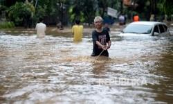 Warga melintas di dekat mobil yang terendam air luapan Sungai Ciliwung, Bukit Duri, Jakarta, Kamis (16/2).