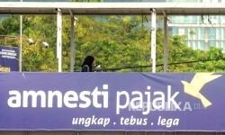 Warga melintas di jembatan penyebrangan orang (JPO) yang terpasang spanduk sosialisai pengampunan pajak di kawasan Stasiun Gambir, Jakara, Ahad (31/7).  (Republika/ Agung Supriyanto)