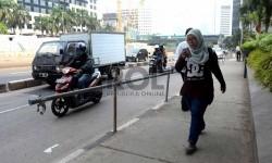 Warga melintas menggunakan trotoar di kawasan Jalan Sudirman, Jakarta Pusat, Jumat (20/11).