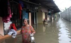 Warga melintasi banjir yang merendam kawasan permukiman Kampung Buaran, Harapan Mulya, Bekasi, Jawa Barat, Minggu (19/2).