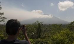 Warga memotret asap yang mulai mengepul dari kawah Gunung Agung dari Pos Pemantauan Desa Rendang, Karangasem, Bali.