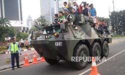 Warga menaiki kendaraan Anoa dalam Pameran Industri Pertahanan saat melintasi Jalan Merdeka Barat, Jakarta, Ahad (13/8).
