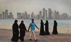 Warga Qatar menikmati berjalan-jalan di pinggir laut di Doha.