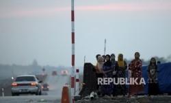 Warga sekitar melihat kendaraan pemudik yang melintas di Jalan darurat Brebes-Gringsing, Jateng, Jumat (23/6).