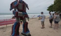 Wisatawan asing melihat boneka robot berbahan botol plastik bekas di Pantai Kuta, Rabu (27/12).