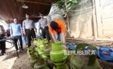 Tersangka menunjukan cara pengoplosan gas saat rilis pengungkapan pabrik pengoplosan tabung gas 3 kilogram ke tabung 12 kilogram dan 50 kilogram di Kawasan Pinang, Tangerang, Banten, Jumat (12/1).