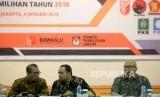 Aggota KPU Ilham Saputra (kanan) menyampaikan pandangannya disaksikan Anggota KPU Hasyim Azhari (kiri) dan Anggota Bawaslu Mochammad Afifuddin (tengah) dalam rapat koordinasi persiapan tahapan pendaftaran pemilihan umum 2018 di Jakarta, Kamis (4/1).