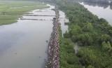 Sebuah foto diambil dari video yang dirilis oleh UNHCR pada 16 Oktober, menunjukkan ribuan pengungsi muslim Rohingya yang melarikan diri dari Myanmar tiba di perbatasan Anjuman, Bangladesh.