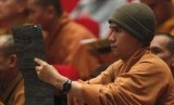A Buddhist monk films, with an iPad, the closing ceremony of the seventh congress of Vietnam's Buddhist Sangha Association in Hanoi November 24, 2012.