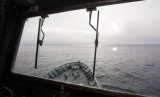 A crew member aboard the Australian Navy ship, HMAS Success, can be seen through a window looking for debris in the southern Indian Ocean during the search for missing Malaysia Airlines Flight MH370.