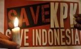 Aktivis Masyarakat Sumut Peduli KPK memegang poster ketika melakukan aksi mendukung Komisi Pemberantasan Korupsi (KPK), di kawasan titik nol Kota Medan, Sumatera Utara, Jumat (23/1)