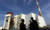 Iranian workers stand in front of the Bushehr nuclear power plant, about 1,200 km (746 miles) south of Tehran October 26, 2010 file photo.