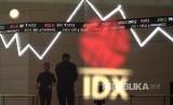 Karyawan melintas di bawah monitor pergerakan Indeks Harga Saham Gabungan (IHSG) Bursa Efek Indonesia, Jakarta. ilustrasi
