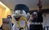 Ketua KPU Arief Budiman bersama maskot gerakan pencocokan dan penelitian (coklit) seusai memberikan keterangan pelaksanaan coklit serentak di Kantor KPU Jakarta, Ahad (14/1).