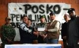 Ketua Pemulihan Bencana Sosial Tolikara, Edi Rante Tasa (kedua kiri) menerima sumbangan sebesar Rp. 100.000 juta dari Manajer Layanan Badan Amil Zakat Nasional (Baznas) Agus Siswanto (ketiga kanan) disaksikan oleh Ketua Tim Pencari Fakta (TPF) Komat Tolika
