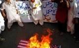 Muslim di Pakistan membakar bendera AS dan meneriakkan slogan anti-Amerika dalam demonstrasi pada 21 Mei 2010.