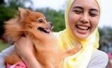 Muslimah Malaysia bermain dengan anjing