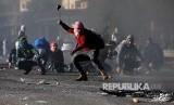 Pengunjukrasa melontarkan ketapel di selu unjuk rasa di Kota Ramallah, Tepi Barat, Palestina, Jumat (8/12)